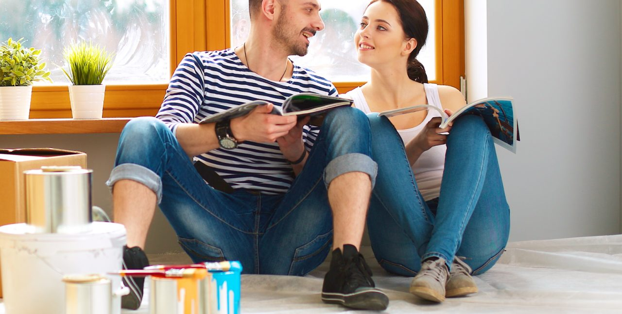 Happy young couple sitting in a new painted house